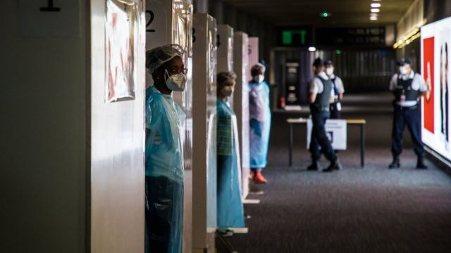 Health workers wearing protective gear wait for incoming travellers to arrive