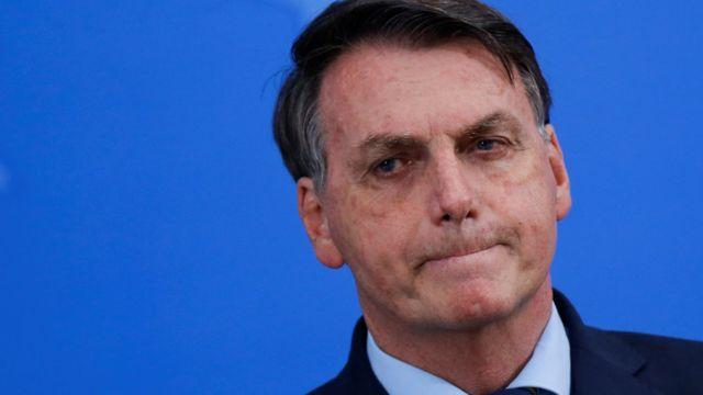 Bolsonaro em frente a painel azul de evento cerrando os lábios