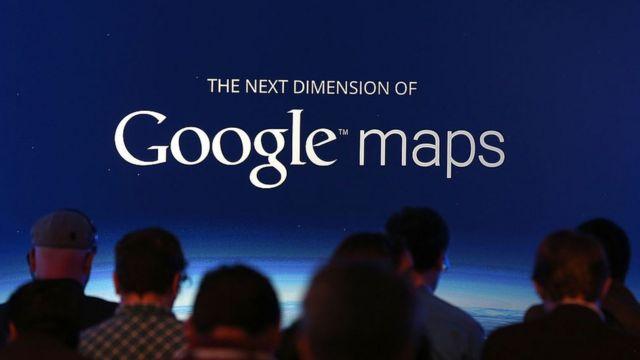 Gente ante un cartel de Google Maps