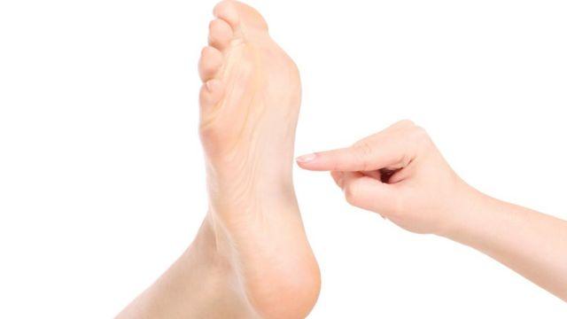 Una mano se acerca a hacerle cosquillas a un pie