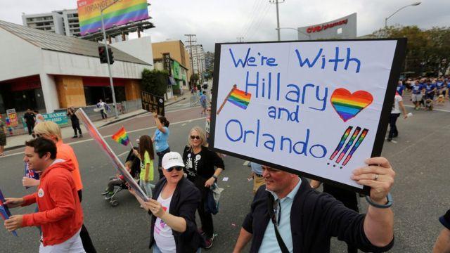 """Un hombre lleva una pancarta que dice """"Estamos con Hillary y Orlando""""."""