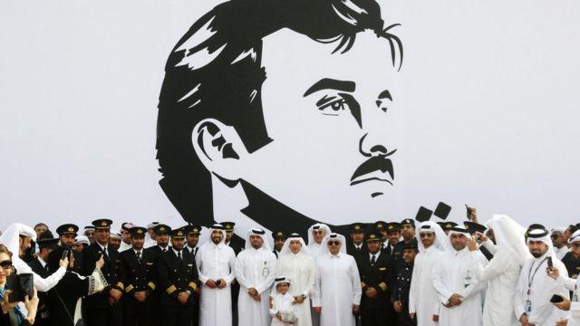 موظفو الخطوط الجوية القطرية أمام صورة الشيخ تميم