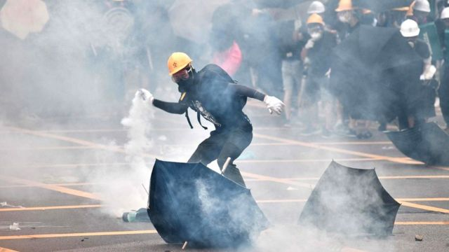 Protester throwing a tear gas can back at the police