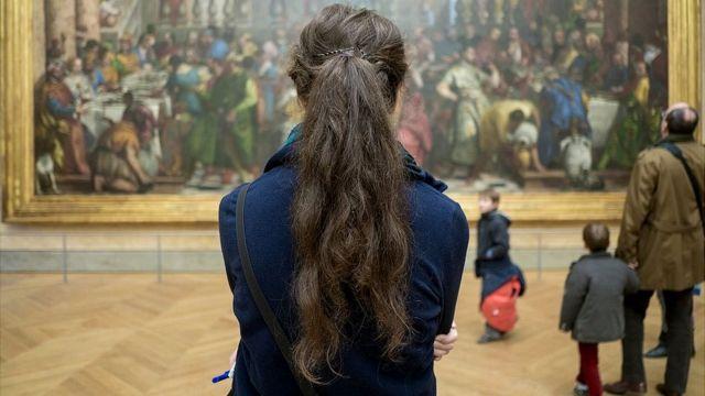Mujer, hombre y niños en el Louvre.