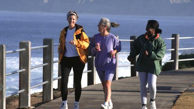 Três mulheres caminhando em um cais
