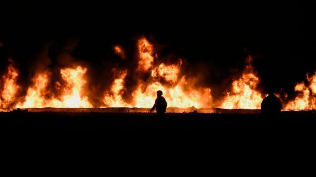 Bombero camina frente a la llamas.