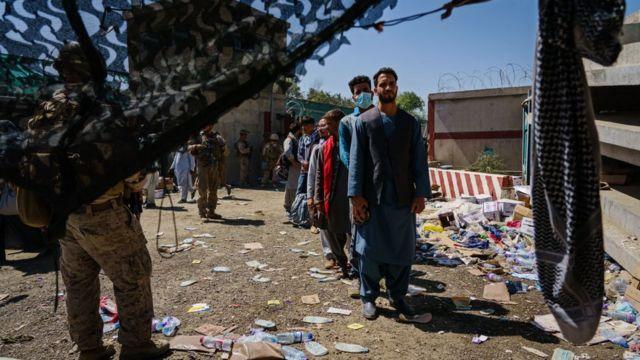 الجنود الأمريكيون يراقبون اللاجئين الأفغان الذين ينتظرون في طابور إجلاءهم في رحلة خروج من كابل