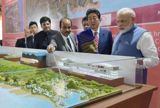 """This handout photograph released by India""""s Press Information Bureau (PIB) on September 14, 2017 shows Indian Prime Minister Narendra Modi (L) and Japanese Prime Minister Shinzo Abe looking at a railway station model at a ground breaking ceremony for the Mumbai-Ahmedabad high speed rail project in Ahmedabad. India""""s first bullet train project, a $19-billion initiative linking Ahmedabad to Mumbai, was launched September 14"""