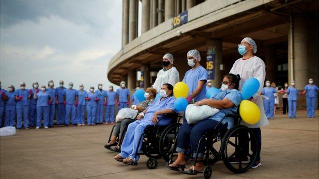 Alzira Neves, Helena Elvira and Marluce de Carvalho acompanhadas por enfermeiros em frente a hospital de campanha no estádio Mané Garrincha, em Brasília, onde receberam tratamento para covid-19REUTERS/Adriano Machado