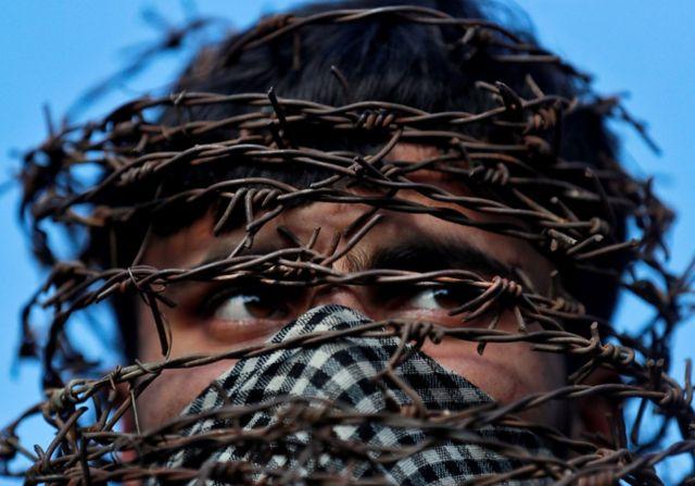 Мужчина в маске из колючей проволоки на протесте в Кашмире