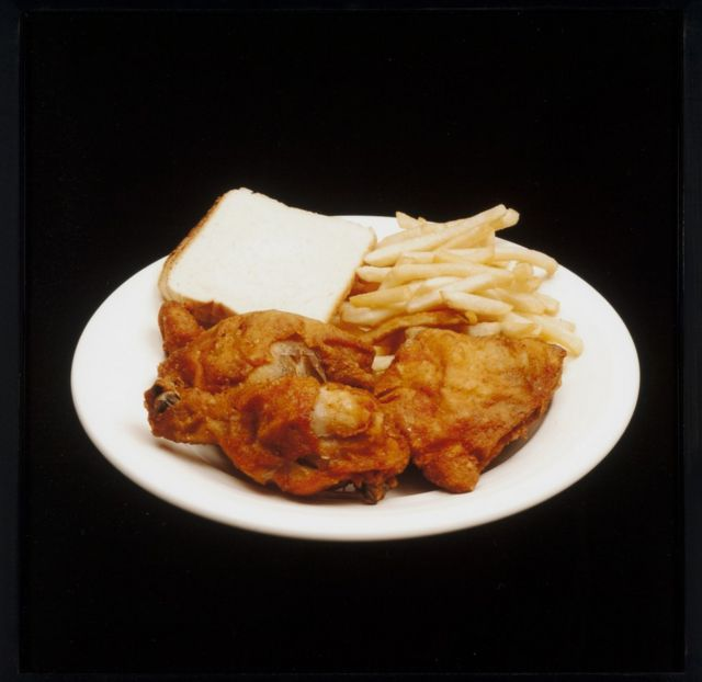A meal featuring french fries, fried chicken and white bread