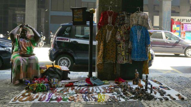 Amina Ngom e seus produtos em calçada do Rio