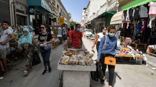 أشخاص يسيرون على طول زقاق في سوق باب الفلاح الشعبي في العاصمة التونسية تونس