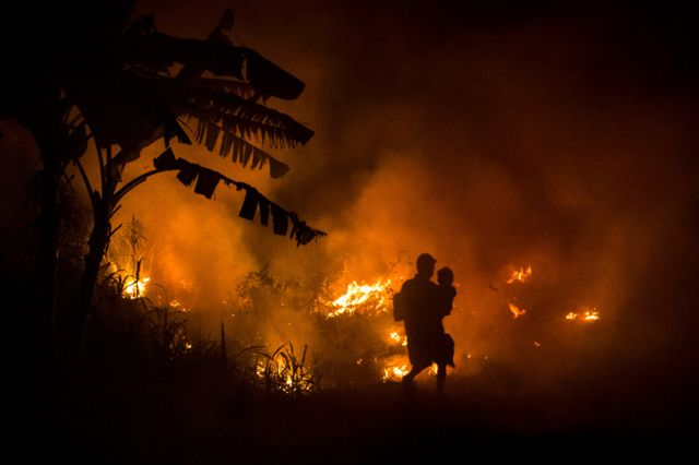 A man carries his son as he walks through the haze on the way to his house as a fire burned peatland in 2015 fires.