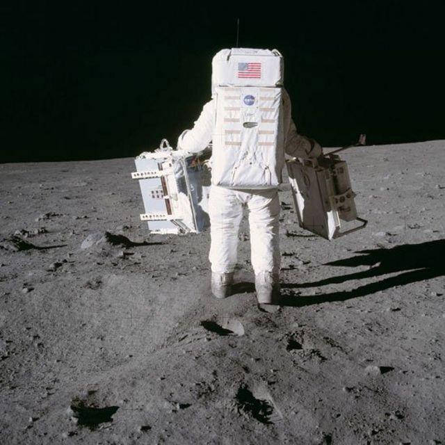 Aldrin carga experimentos antes de desplegarlos sobre la superficie de la Luna.