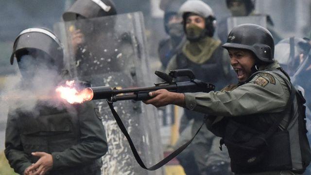 Um membro da Guarda Nacional venezuelana disparando arma