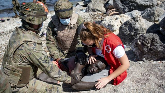 A medical assistant treating a migrant in the Ceuta area on May 18, 2021.
