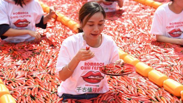 Una mujer come chiles en un concurso en China