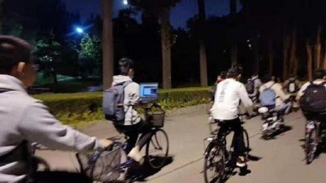 Em uma das fotos, um estudante da Universidade de Tsinghua usava seu laptop enquanto andava de bicicleta