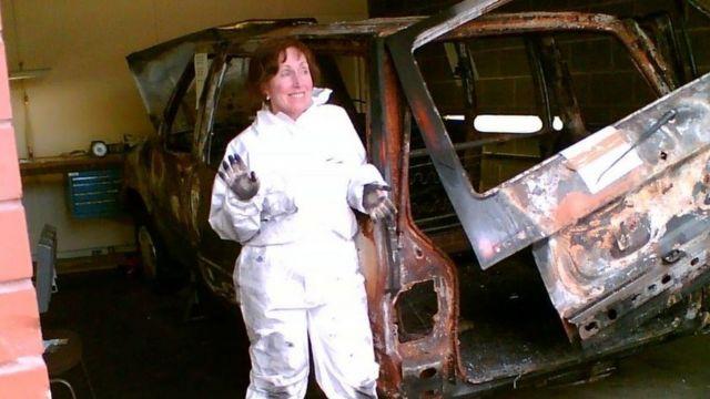 Wiltshire com jaleco, sorrindo e mostrando a mão suja de carvão ao lado de um carro queimado