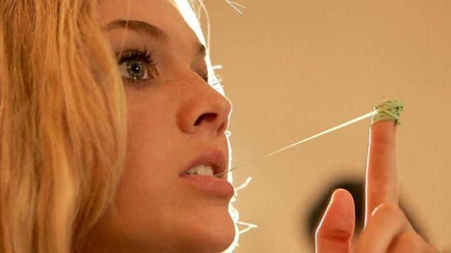فتاة تتلاعب بعلكة في فمها