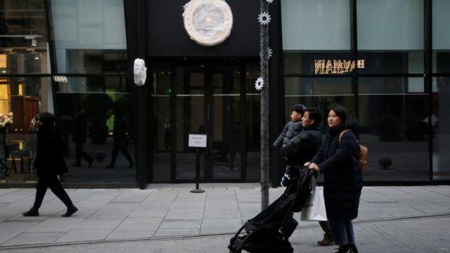 Peatones pasando por una tienda canadiense cerrada en Pekín.