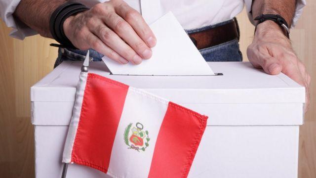 mão coloca cédula em urna de votação, com bandeira do peru em frente