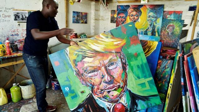 Kenyan artist Evans Yegon aka 'Yogonizer' carries one of his painting of USA President-elect Donald Trump at his workshop December 15, 2016 at the GoDown art Centre in Nairobi