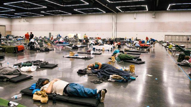 Personas en camas en un refugio durante la ola de calor en Oregon