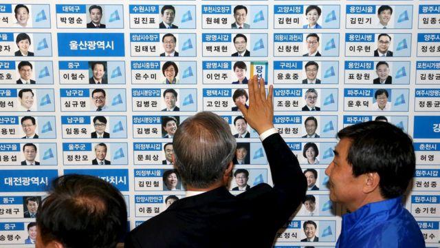 当選者の名前の横にシールを張る「共に民主党」の幹部ら(13日、ソウル)