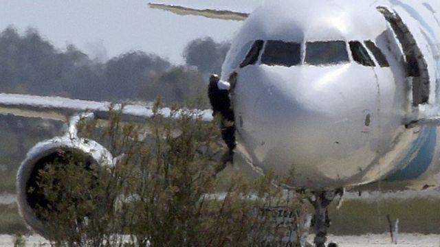 Man climbs from aircraft cockpit
