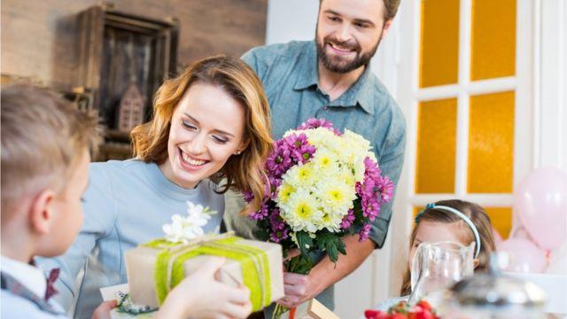 Una madre recibe regalos, tarjetas y flores de sus hijos y esposo en el Día de la Madre