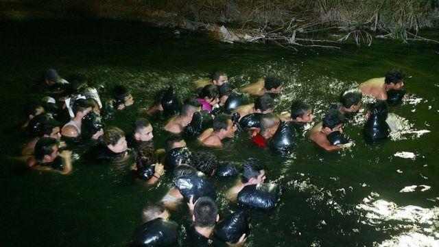 Grupo de imigrantes vindo do México num rio em 2006 tentando entrar em Calexico, California