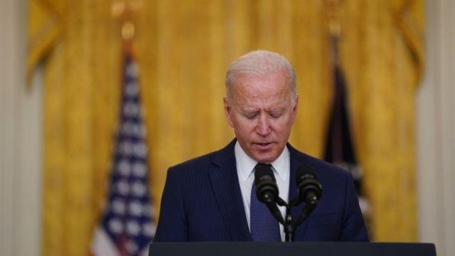 Biden em pé discursando em frente a microfone na Casa Branca