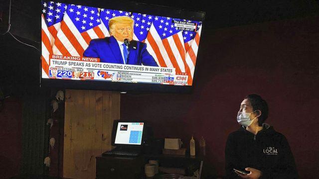 北京酒吧里的一名女服务员正在观看美国大选直播。