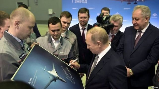 रशियाचे अध्यक्ष व्लादिमीर पुतिन स्वाक्षरी करताना