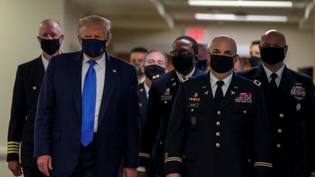 Trump e militares de máscara caminham em corredor de hospital