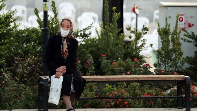 Mujer con mascarilla en Teherán