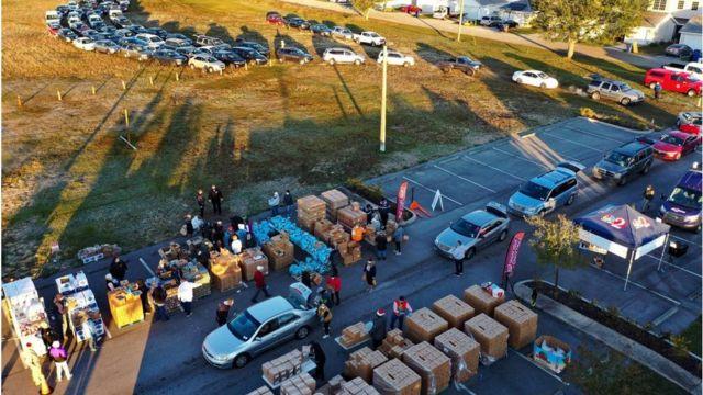 Voluntários carregam caixas em um evento de distribuição de alimentos na Flórida
