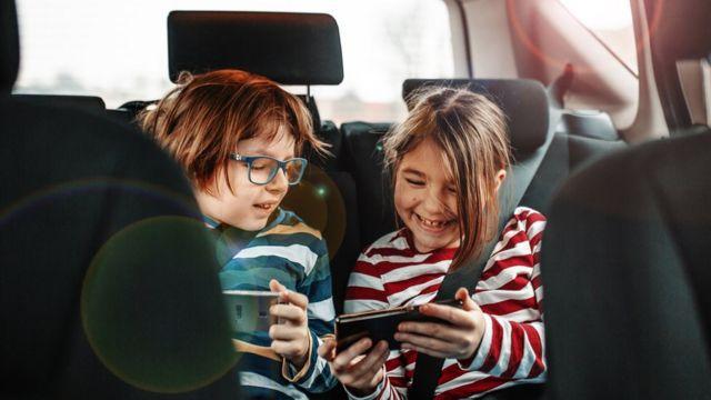 niños usando teléfono móvil