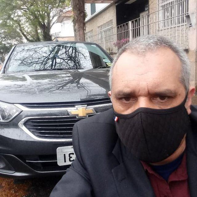 De máscara, Rosemar na frente do carro que usa para trabalhar como motorista de aplicativo