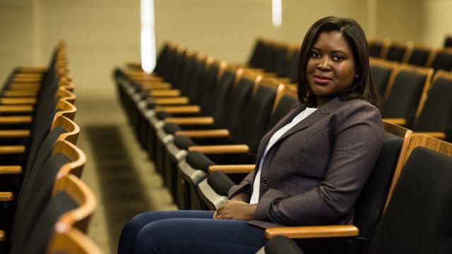 A economista Vilma Pinto posa para foto sentada em uma cadeira em meio a fileiras com várias outros assentos