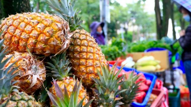 A hawker selling pineapples seen in the street of Taipei
