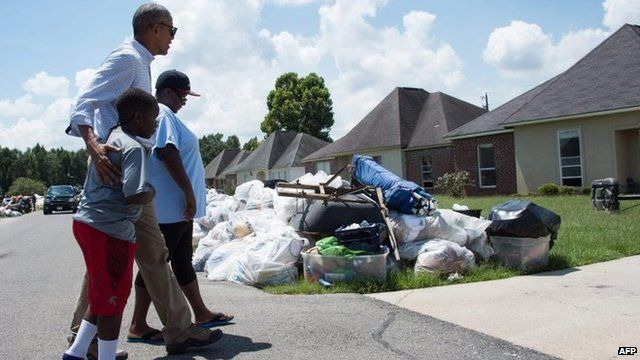President Barack Obama walks with residents as he tours a flood-affected area in Baton Rouge, Louisiana.