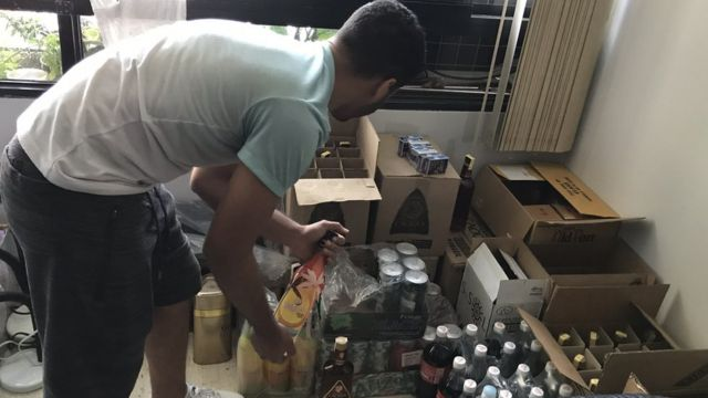 Cristian Roa picking up a bottle from some boxes.