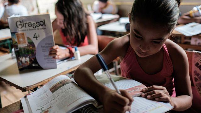 Niñas escriben en pupitres en una escuela en Brasil