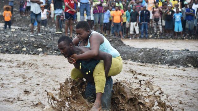 Un hombre transporta a una mujer para cruzar un río en Petit Goave, al suroeste de Puerto Príncipe.