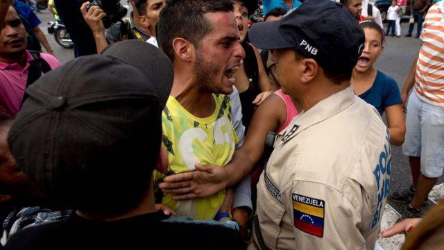 Manifestante le grita a un policía venezolano.
