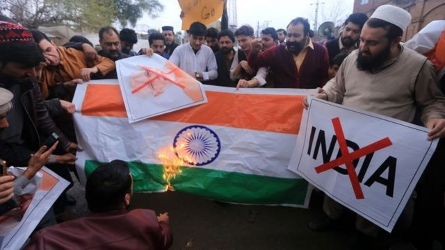 Protesters in Pakistan burn Indian flags and hold up signs, angry at an Indian incursion into Pakistani territory