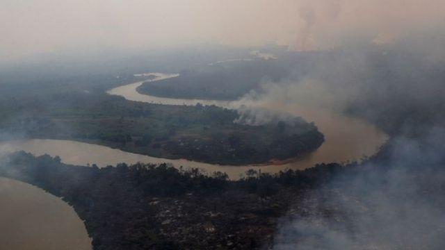 Vista aérea de rio no Pantanal, com florestas nas margens pegando fogo